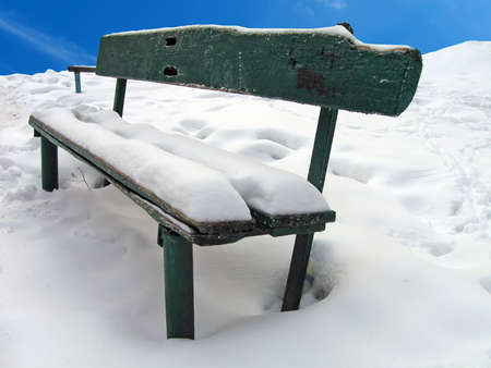 one vintage green wood bench under white snow and blue sky, footprints, winter details photo