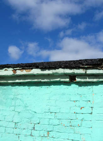 rosin: old green brick wall with pitched black roof on blue sky with white clouds, vintage construction details