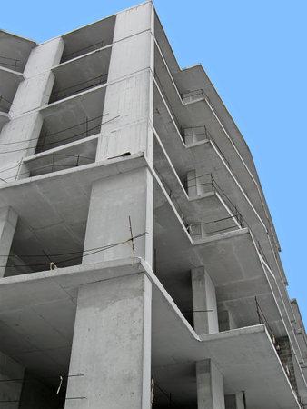 realestate: modern construction site on blue sky, concrete skyscrapper building details