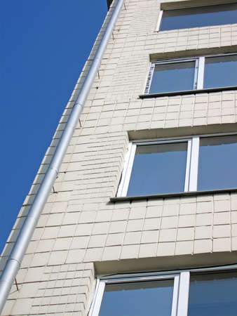 new building with metal pipe and glass windows on blue sky in sunny day, urban real estate construction photo