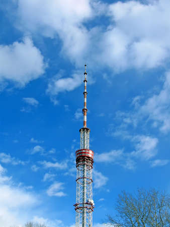 high telecommunication pylone on blue sky with many white clouds, telecommunication details photo