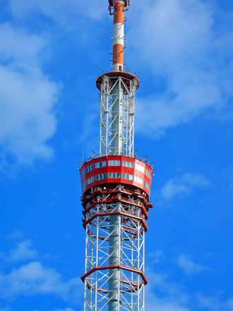 high telecommunication red pylone on blue sky with many white clouds, tower details photo