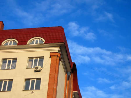 one new colorful yellow brick building with red roof on blue sky. new construction details Stock Photo - 13567730