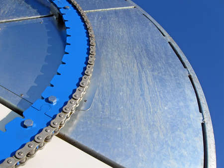abstract blue industrial metal wheel with steel chain on blue sky, industry details photo