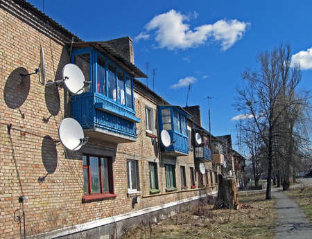 long brick building with many satellite antennas on the wall and roof, environment details photo
