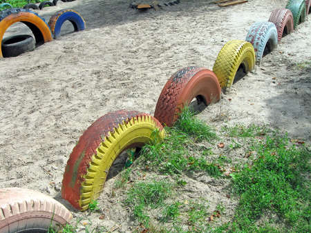 abstract refused color painted tyre heap on sand, modern recycling concept photo
