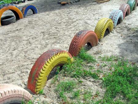 refused: abstracta se neg� color pintado mont�n de neum�ticos en la arena, el concepto del reciclaje Foto de archivo