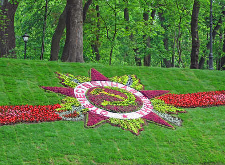 Great Patriotic War star sign from different colorful flowers on green grass background near Mariinsky park in Kiev city, may 09, 2010. text on russian from colorful flowers Stock Photo - 13685396