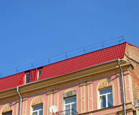 old brick building with red roof, metallic pipes on blue sky  new construction concept photo