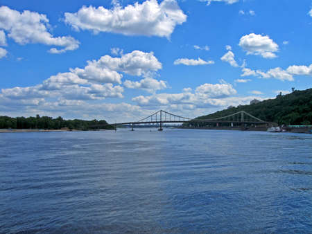 dniper: Bridge on Dniper river under white cumulus clouds