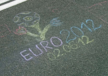 KIEV - JUNE 02: Euro 2012 football emblem painted by chalk (graffiti) on asphalt on June 02, 2012 in Kiev, UKRAINE. Sport sign devoted to EURO 2012 Football Championship in Ukraine and Poland in summer 2012. Stock Photo - 14140953