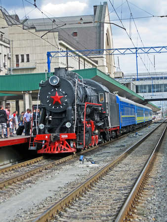 KIEV, UKRAINE - JUNE 27: Retro black steam engine with blue wagon line on the Central Railway Station on June 27, 2012 in Kiev, UKRAINE. First retro train in Kiev available for travel daily since June 10.