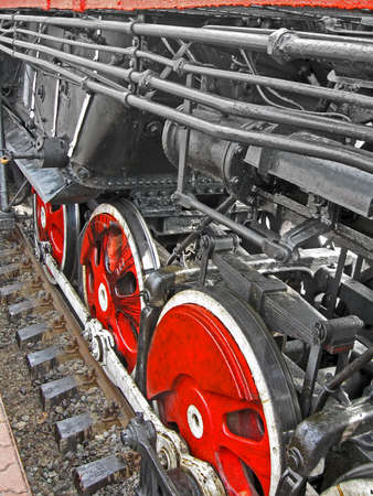 pile engine: red round steam engine wheels with hanging ovehead and metal connected pipe heap, nostalgia details