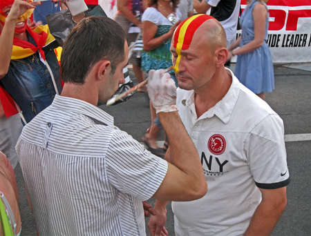 KIEV - JULY 01: Painter draw the national flag on face of fan before final match Spain-Italy on July 01, 2012 in Kiev, UKRAINE. Later this day Spain football team became UEFA EURO 2012 Winner. Stock Photo - 14326916