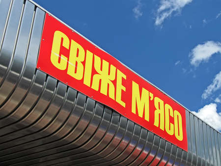 fresh meat as text on ukrainian language, red signboard on blue sky with white clouds