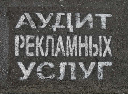 advertising service audit as white painted text on russian on grunge asphalt, modern communication details Stock Photo - 14892584