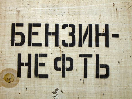 benzin: focus on center  benzin, oil as text on russian language on grunge metal surface, fuel details
