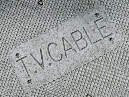 focus on center. tv cable television as text on vintage metal manhole, modern telecommunication details photo