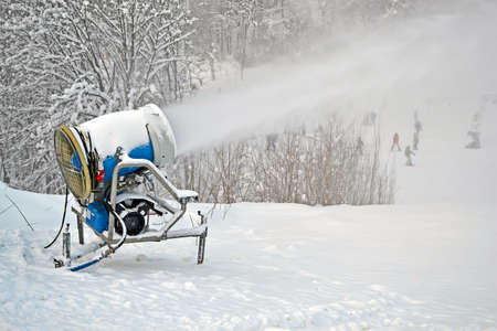 snow gun (pulverizer) disperse artifitial snow on mountain, seasonal environment details photo