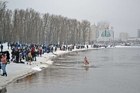 KIEV - JAN 19: Epiphany (Kreshchenya) in Hydropark on January 19, 2013 in Kiev, Ukraine. People plunging into ice-cold water three times as it helps body became more resilient to illness. Epiphany known since 988 AD.