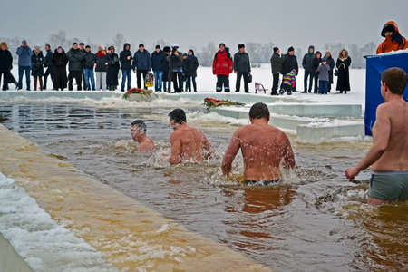 sanctification: Epiphany (Kreshchenya) morning near Svjato-Pokrovskiy Cathedral on January 19, 2013 in Kiev, Ukraine. People plunging into ice-cold water three times as it helps body became more resilient to illness. Epiphany known since 988 AD.