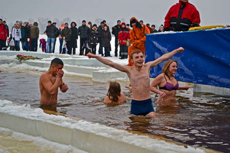 sanctification: Epiphany (Kreshchenya) near Svjato-Pokrovskiy Cathedral on January 19, 2013 in Kiev, Ukraine. Smiling people in ice-cold water. Epiphany known since 988 AD.
