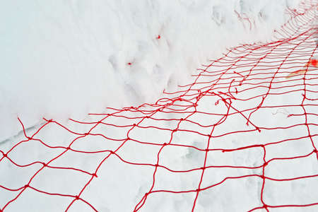 focus on center  damaged red yarn grid under white snow, winter season details Stock Photo - 17757521