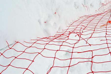 focus on center  damaged red yarn grid under white snow, winter season details Stock Photo - 17757521
