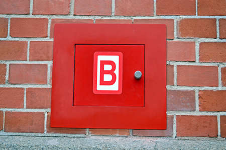 red fire box for hydrant on the red brick wall, modern security details photo