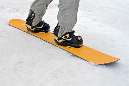 sportsman with yellow snowboard on white snow, seasonal sport details