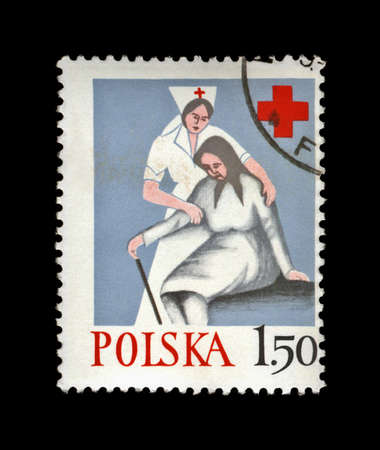 POLAND - CIRCA 1977, JAN 24: canceled stamp printed in Poland, shows nurse help old woman, Polish Red Cross, circa 1977. vintage post stamp isolated on black background.