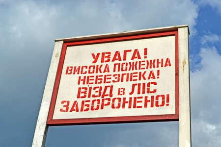 no entrance: atenci�n de alto riesgo de incendios no entrada del bosque como el mensaje de alarma roja en el tablero de madera en el idioma ucraniano Foto de archivo