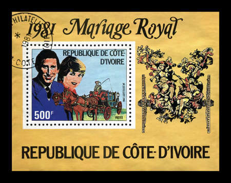 lady diana: Lady Diana Spencer and Prince Charles marriage , circa 1981. cancelled vintage postal stamp printed in Cote-Divoire Ivory Coast isolated on black background.