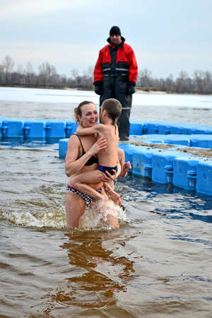 baptizing: woman with kid in cold water during Epiphany near Svjato-Pokrovskiy Cathedral on January 19,2014 in Kiev,Ukraine. People plunging into ice-cold water as it helps body became resilient to illness.Epiphany known since 988 AD. Editorial