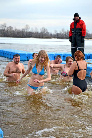 baptizing: Epiphany near Svjato-Pokrovskiy Cathedral on January 19,2014 in Kiev,Ukraine.People plunging into ice-cold water as it helps body became resilient to illness.Epiphany known since 988 AD.