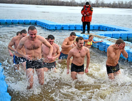 man in cold water during Epiphany near Svjato-Pokrovskiy Cathedral on January 19,2014 in Kiev,Ukraine.People plunging into ice-cold water as it helps body became resilient to illness.Epiphany known since 988 AD.