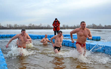 baptizing: man running in cold water during Epiphany near Svjato-Pokrovskiy Cathedral on January 19,2014 in Kiev,Ukraine.People plunging into ice-cold water as it helps body became resilient to illness.Epiphany known since 988 AD.