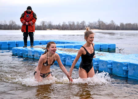 baptizing: few female in cold water, Epiphany near Svjato-Pokrovskiy Cathedral on January 19,2014 in Kiev,Ukraine.People plunging into ice-cold water as it helps body became resilient to illness.Epiphany known since 988 AD. Editorial