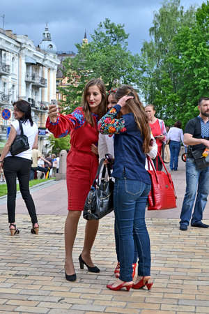 KIEV, UKRAINE - MAY 28: Unknown young females in national costumes make the selfie during Embroidery dress (Vyshyvanka) parade on May 28, 2016 in Kiev, Ukraine.