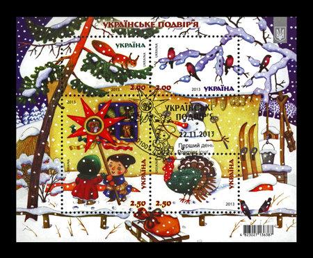 UKRAINE - CIRCA 2013: cancelled stamp printed in Ukraine shows Ukrainian village on Christmas, circa 2013. vintage post stamp isolated on black background.