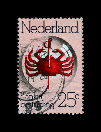 Pierced red crab under lens, anniversary of Cancer Research Fund, stamp of Netherlands, circa 1974 Stock Photo