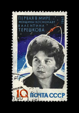 Valentina Tereshkova, soviet astronaut, 1st woman in the space, rocket shuttle, USSR, circa 1963. canceled vintage post stamp printed in Soviet Union isolated on black background. Editorial