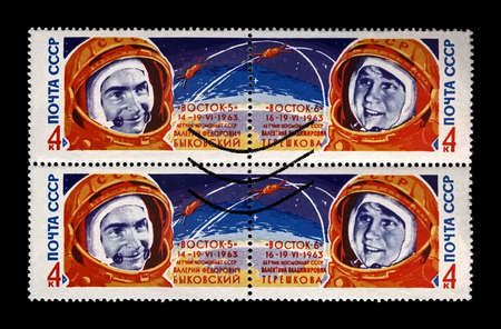 Valery Bykovsky and Valentina Tereshkova, soviet astronaits, rocket shuttle Vostok 5 and 6, circa 1963. canceled vintage post stamp printed in USSR (Soviet Union) isolated on black background. Editorial