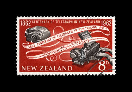 telegraph device and encoded paper tape, 100th anniversary of inauguration of the telegraph in New Zealand, circa 1962.  canceled vintage postal stamp printed in New Zealand isolated on black background. Archivio Fotografico - 97313176