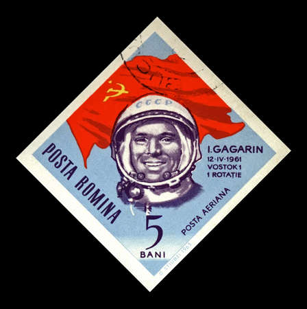 ROMANIA - CIRCA 1964: canceled stamp printed in Romania shows soviet astronaut Yuri Gagarin, 1st man in the space, red soviet flag, circa 1964. vintage postal stamp isolated on black background.