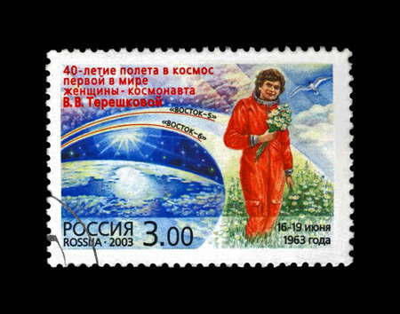 Valentina Tereshkova in red uniform with flowers, soviet astronaut, 1st woman in the space, blue sky, 40th anniversary of the space flight, circa 2003.  canceled vintage postal stamp printed in Russia isolated on black background.
