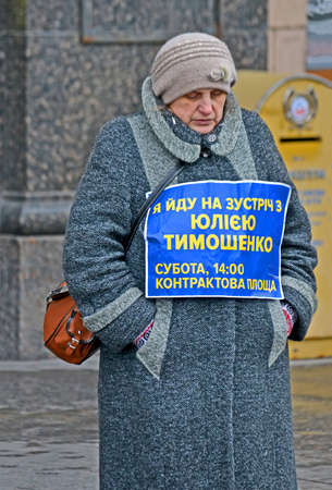 KIEV, UKRAINE - FEB 08, 2019: Unknown woman in grey coat with Julia Timoshenko pre-elections meeting message on February 08, 2019 in Kiev, Ukraine. Meeting take place on Saturday, 2p.m. at Kontraktova square, Podol district. Sajtókép