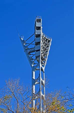 powerful lighting spotlight construction pylon near stadium on blue sky in sunny day, environment diversity