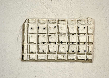 metal grid cover with hole heap closeup on white stone wall, restricted area diversity