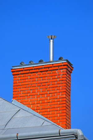 orange chimney brick pipe on the roof on blue sky in sunny day, modern construction, environment pollution diversity